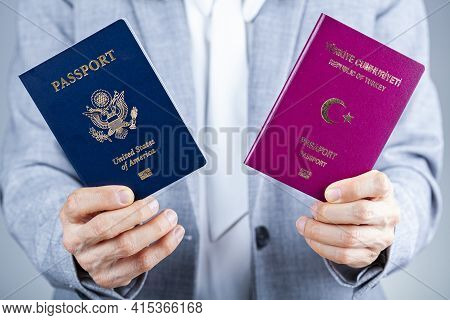 A Woman In Formal Clothes Is Holding Turkish And Us Passports. Concept Image For Immigration To Usa,