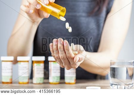 A Young Depressed Woman Is Taking Pills Out Of The Medication Bottle. She Has A Stack Of Bottles Lin