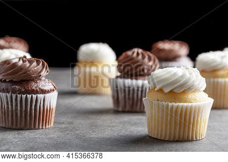 Side View Image Of Vanilla And Chocoloate Cupcakes On Dark Stone Countertop Against Black Background