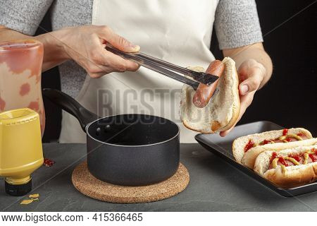 A Caucasian Woman Is Taking A Fresh Boiled Hot Dog Sausage From A Pot  Using Metal Tong In Order To
