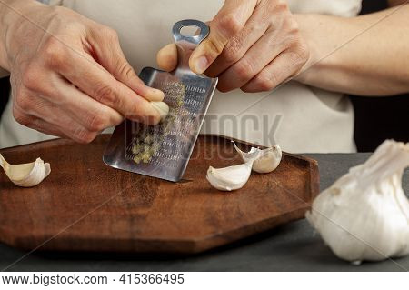 Hands Of A Caucasian Woman Grating Garlic Cloves Using Shovel Shaped Metal Mini Grater On A Wooden P