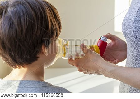 A Caucasian Woman Is Giving Emergency Asthma Medication To A Small Kit During An Attack. She Uses Ae
