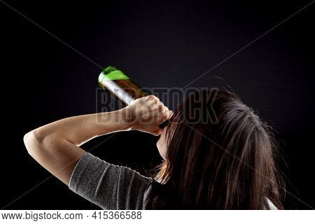 Rim Light From Behind Image Of A Young Caucasian Woman Drinking Beer From Bottle Against Dark Backgr