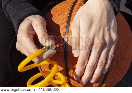 Close Up Image Showing A Caucasian Woman Holding A Basketball And Inserting Needle Bit At The End Of