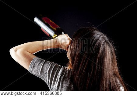 Rim Light From Behind Image Of A Young Caucasian Woman Drinking Wine From Bottle Against Dark Backgr
