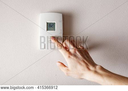 A Woman Is Pressing The Up Button Of A Wall Attached House Thermostat With Digital Display Showing T