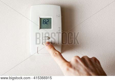 A Woman Is Pressing The Down Button Of A Wall Attached House Thermostat With Digital Display Showing