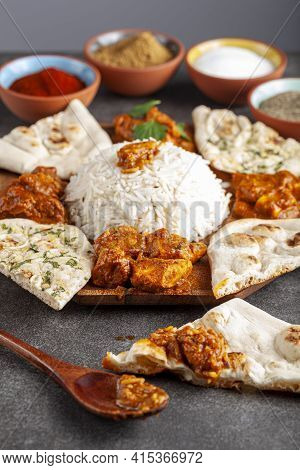 Angled Image Of A Gourmet Mixture Of Indian Dishes Including Rice, Naan, Tikka Masala, Butter Chicke