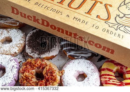 Clarksburg, Md, Usa 03-04-2021: A Cardboard Box Of A Dozen Donuts Bought From The Chain Store Duck D