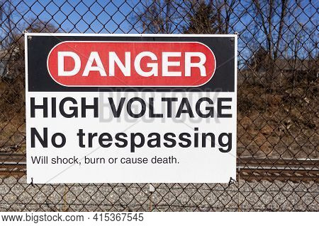 Danger, High Voltage, No Trespassing Sign On A Fence In Front Of A Rail Road. It Lists Possible Heal