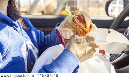 A Woman Is Eating Chicken Sandwich Which She Got From A Roadside Drive Through Fast Food Chain. She