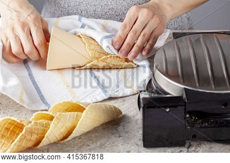 A Caucasian Woman Is Rolling Handmade Waffle Cones Fresh Out Of Waffle Cone Maker Press Machine. She