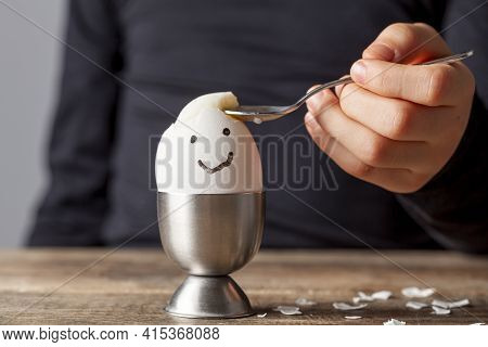A Small Child Is Eating Soft Boiled Humpty Dumpty Egg Placed In Egg Cup On A Wooden Breakfast Table.