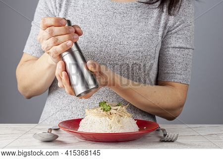 A Woman Is Grinding Peppercorns Using A Cylindrical Hand Grinder On Top Of Traditional Chicken Pilaf