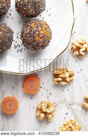 Flat Lay View Of Kitchen Countertop With A Flat Porcelain Plate. Homemade Fresh Carrot Bliss Balls (