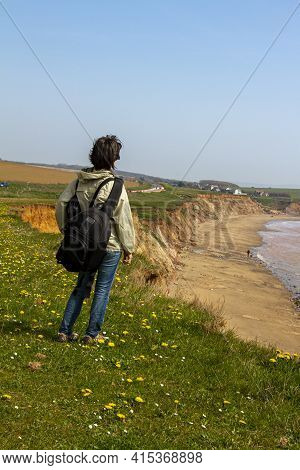 Vertical Photo Of A Woman Hiker With A Backpack As She Stands Alone On Top Of The Cliffs Of Isle Of