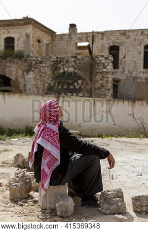 Hama, Syria 04-02-2010: A Young Arabic Man Wearing Keffiyeh And Black Jubba Thobe Dress Is Sitting O