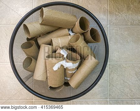 Flat Lay Top View Image Of A Metal Trash Bin Full Of Empty Toilet Paper Rolls With Some Paper Leftov