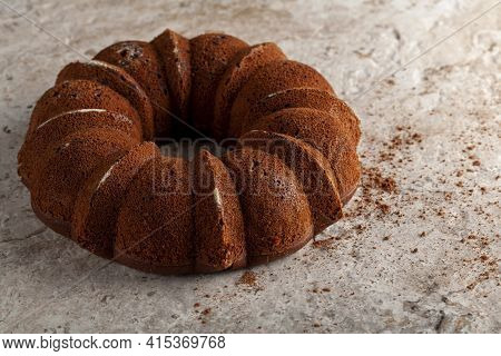 A Round Sponge Cake Fresh Out Of Oven With Crumbles And Cacao Powders Cooling On Top Of A Marble Or