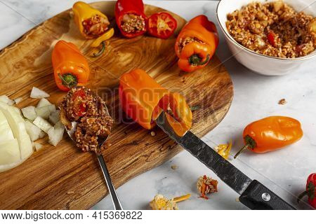 Making Of Stuffed Peppers Using Colorful Red Orange And Yellow Peppers With Seeds Taken Out With Kni
