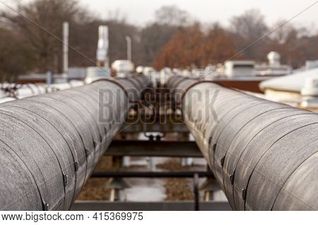 Close Up View Of A Pipeline Running Over Snowy Terrain Near An Energy Plant. Heavy Duty Metal Pipes