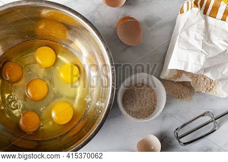 Pastry Being Prepared On Marble Kitchen Countertop With A Paper Bag Of Wholewheat Flour, Broken Egg