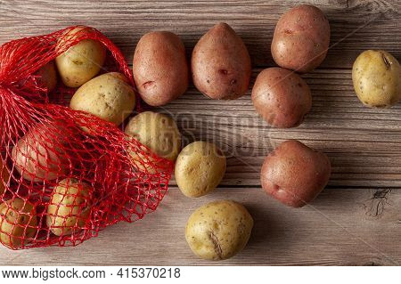 Flat Lay  Close Up Image Featuring A Red Mesh Potato Sack With Pink And Yellow Raw Organic Potatoes