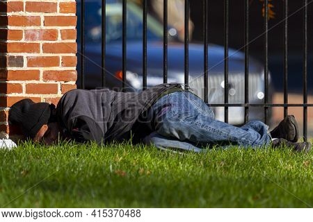 Alexandria, Va, Usa  11-28-2020: A Homeless Latino Man Wearing Sweatshirt And Jeans Is Sleeping On T