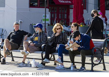 Alexandria, Va, Usa 11-28-2020: A Group Of People Are On Bench At A Crowded Place Snacking On Nibble