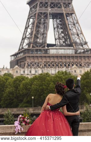 Soon To Be Married Young Couple Is Posing In Front Of The Iconic Eiffel Tower For Their Wedding Phot