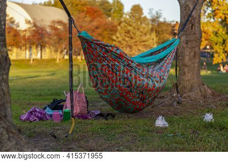 An Autumn Scene In A Park With A Colorful Hammock Set Between Trees And Someone Is Sleeping In It. A