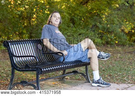 Frederick, Md, Usa 10/14/2020: Long Haired Middle Aged Man Is Relaxing On A Park Bench After A Hike.