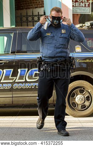 Ellicott City, Md, Usa 10/07/2020: A Young Caucasian Male Police Officer Is Crossing The Street. He
