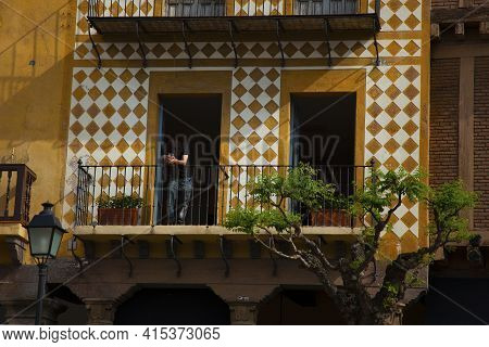 View Of A Stylish Balcony At A Residential Vintage Apartment With Vibrant Facade. There Is A Young M