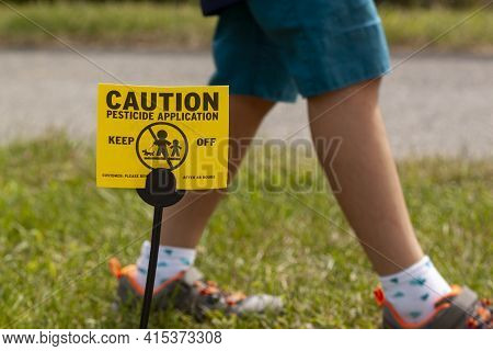 A Yellow Yard Sign Warning Kids And Pets Of The Recent Pesticide Spraying And Advices Them To Stay A