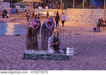 Aqaba, Jordan 03/31/2010: Three Arabic Men In Ethnic Clothes Are Performing The Evening Prayer On Tr