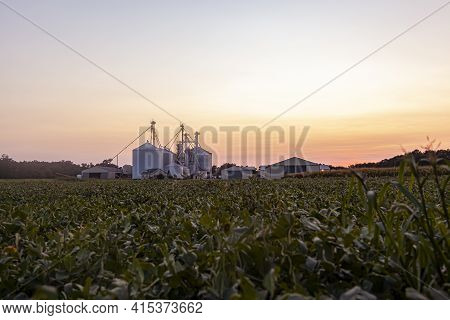 A Sunset View Of The Modern Granaries And Silos Of A Large Industrial Size Farm Which Specializes In