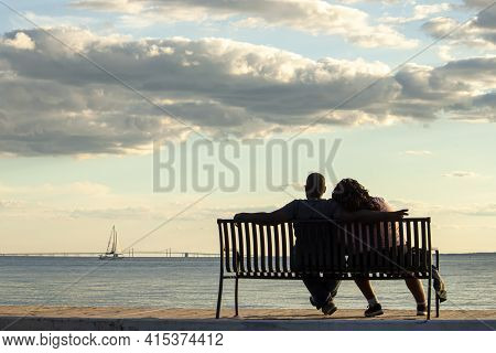 A Young African American Couple Is Sitting On A Bench Looking At Sea And Chesapeake Bay Bridge. Man