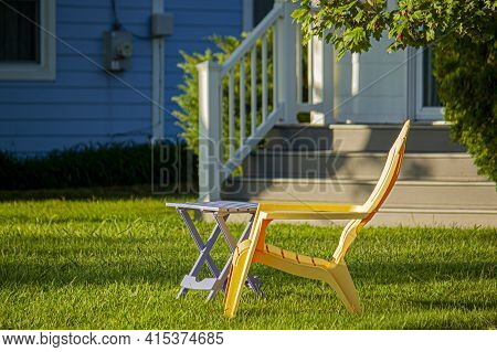 Close Up Image Of A  Simple Yellow Plastic Chair And A Foldable Table Placed Outdoor At The Front Ya