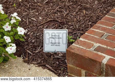 Close Up Image Of A Funny And Creative Yard Sign Placed Among Wood Chips On The Front Yard Of A Hous