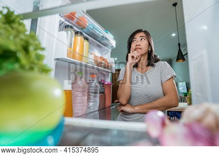 Asian Woman Thinking While Open The Refrigerator Door Before Cooking