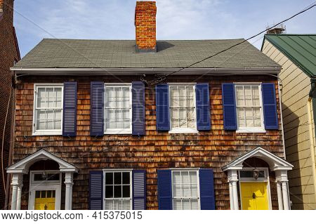 Annapolis, Md 08/21/2020: A Vintage Semidetached House With Wooden Tile Exterior And Dark Blue Windo