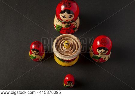 Upper Halves Of Wooden Russian Dolls Are Placed On Dark Background While Lower Haves Were Put Togeth
