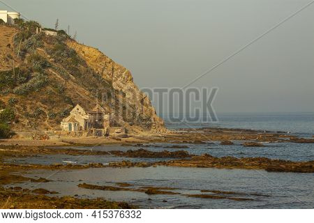 A Rugged Rocky Coast With An Abandoned Stone House On The Foothills Of A Mountain, By The Mediterran