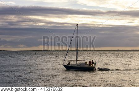 Anglesey, Wales, Uk 08/26/2012: A Small Boat With Three Passengers In It Is Sailing Off The Coast Of