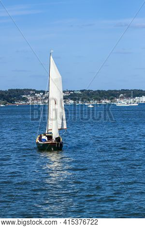A Few People Are On A Small Wooden Boat Sailing Full Sails Ahead. It Is A Sunny Afternoon And Sea Is