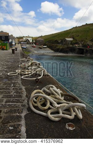 Close Up Image Of Tangled  Mooring Ropes Tied To Metal Rings On A Stone Dock. These Ship Ropes Are U