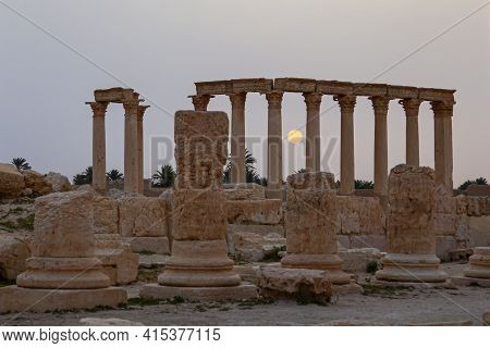 Sun Rises Between The Stone Pillars Of The Ancient Ruins In Palmyra, Syria. Image Taken At Dawn With
