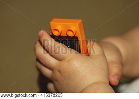Close Up Image Of An Infant Baby's Hands As He Or She Is Trying To Put Together Blocks. Image Is Use