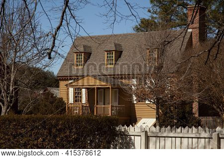 Virginia, Usa 02/24/2014: A Colonial Era House With Brick Chimney Wooden Window Shutters, Porch And